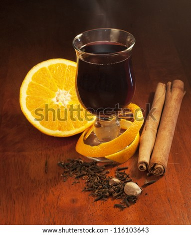 Mulled wine with orange and spices on dark background - stock photo