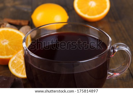 Mulled wine with orange and spices on wooden background - stock photo