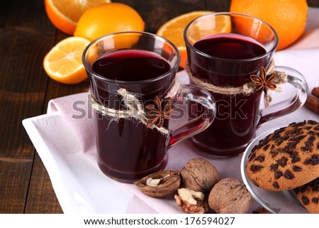 Mulled wine with oranges and cookies on table close up - stock photo