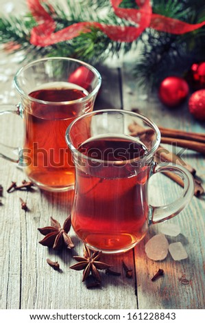 Mulled wine with spices and christmas decoration on wooden background - stock photo