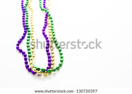 Multi color Mardi Gras beads on white background. - stock photo