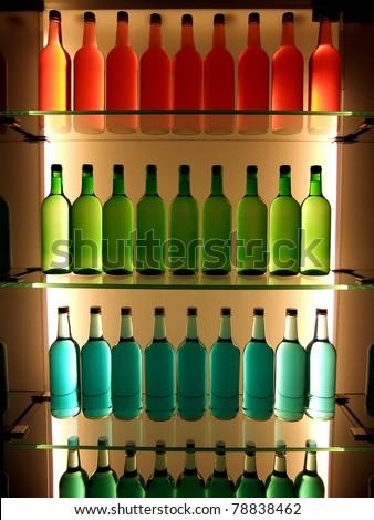 Multi-colored bottles on glass shelves - stock photo
