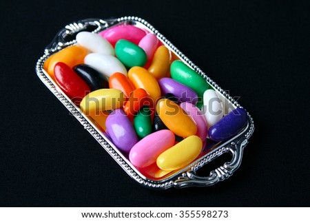 Multi colored candies on a tray with black background - stock photo