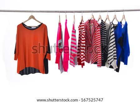 Multi colored female shirts with striped on hangers against a white background  - stock photo