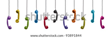 Multi colored handset pieces suspended by the phone cord, isolated on white background - stock photo