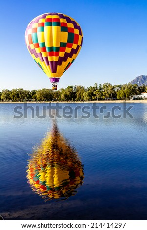 Multi-colored hot air balloon with bright blue sky flying over lake with reflection - stock photo