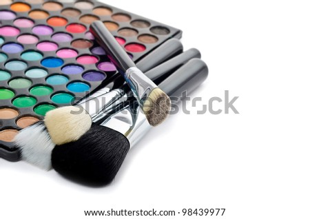 Multi colored make-up and brushes isolated on white - stock photo