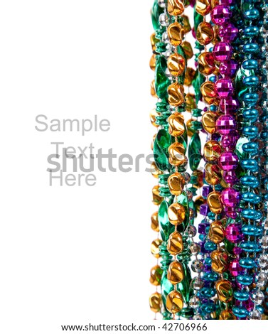 Multi colored mardi gras beads including blue, green, purple, pink, yellow and gold on a white background with copy space - stock photo