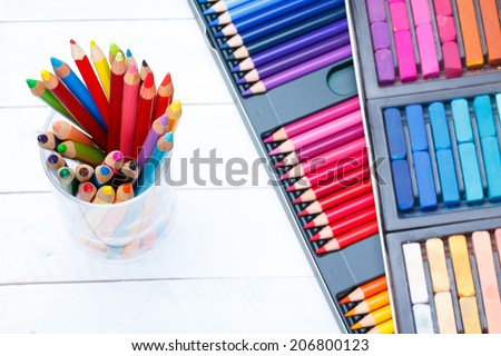 Multi colored pencils in jar on wooden table, with pastel and pencils box on background - stock photo