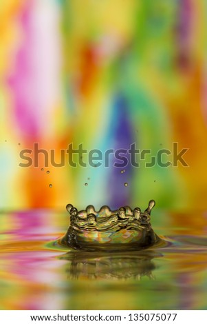 Multi-colored tie dye reflected in water splash - stock photo