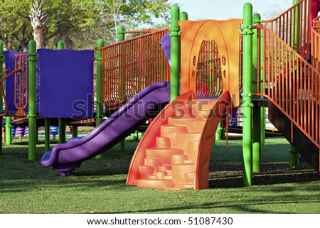 Multi-colored vibrant playground equipment with slide, steps and bars - stock photo