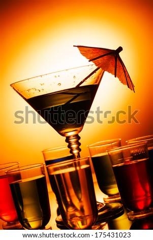 Multi-coloured alcohol shots and martini glass - stock photo
