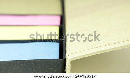 Multi-coloured block of post it note or sticky note stickers with a holder case. Slightly defocused and close-up shot. - stock photo
