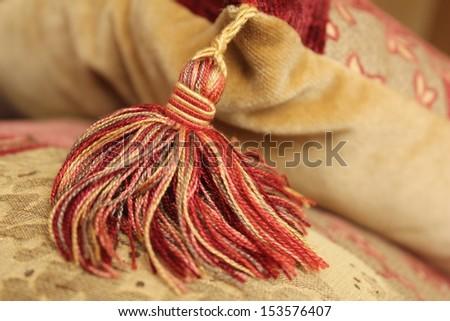 Multi-coloured tassel hanging from the corner of a gold velvet cushion - stock photo