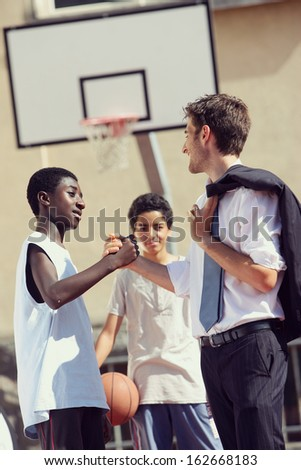 Multi-Ethnic Basketball players shaking hands after match - stock photo