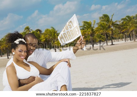 Multi-ethnic bride and groom at beach - stock photo