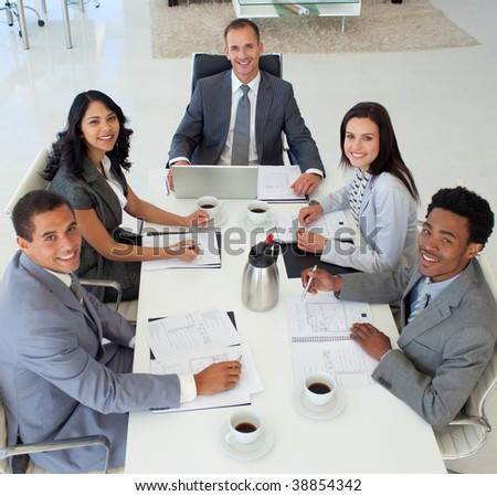 Multi-ethnic business people in a meeting smiling at the camera - stock photo