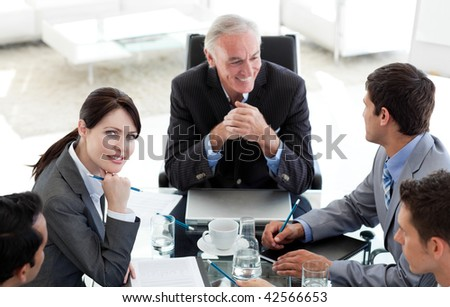 Multi-ethnic business people sitting around a conference table discussing a business plan - stock photo