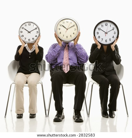 Multi-ethnic business people sitting holding clocks over faces. - stock photo