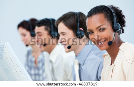 Multi-ethnic business people using headset in a call center - stock photo
