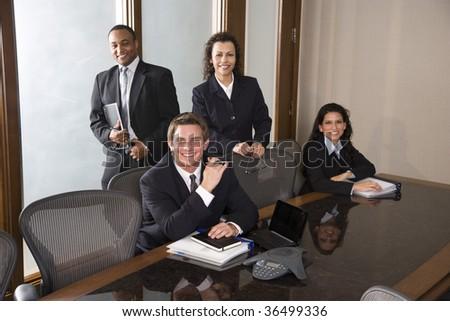Multi-ethnic business team in boardroom - stock photo