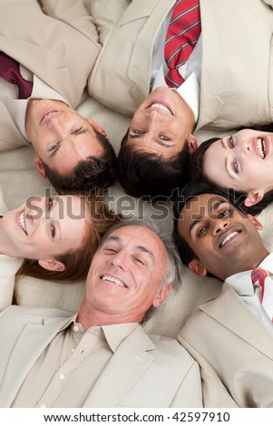 Multi-ethnic business team lying in a circle with heads together - stock photo