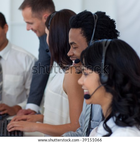 Multi-ethnic business team working in a call center with a manager - stock photo