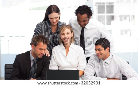 Multi-ethnic business team working with a laptop in an office - stock photo
