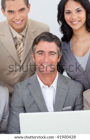 Multi-ethnic business team working with a laptop in office together - stock photo