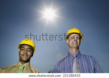 Multi-ethnic businessmen wearing hard hats - stock photo
