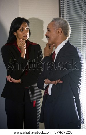 Multi-ethnic businesspeople having discreet conversation in corner of meeting room - stock photo