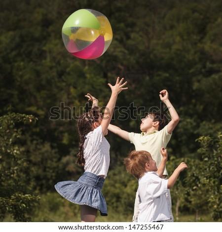 Multi-ethnic children playing ball - stock photo