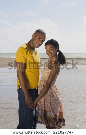 Multi-ethnic couple holding hands at beach - stock photo