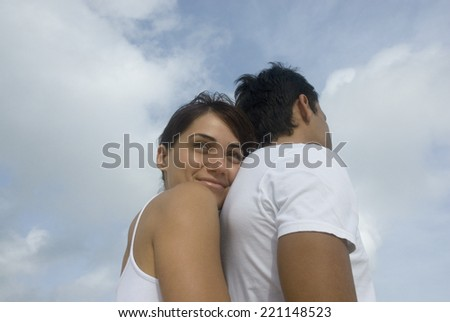 Multi-ethnic couple hugging - stock photo