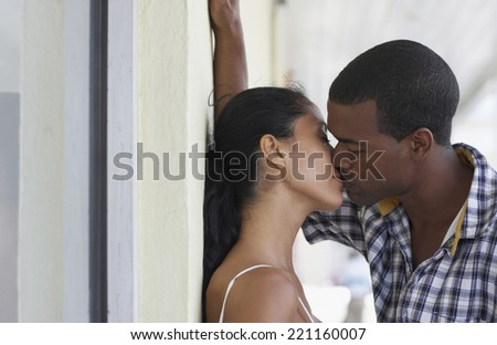 Multi-ethnic couple kissing - stock photo