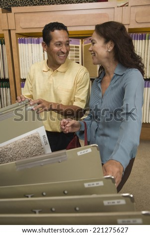 Multi-ethnic couple looking at flooring samples - stock photo