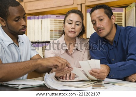 Multi-ethnic couple looking at swatches - stock photo