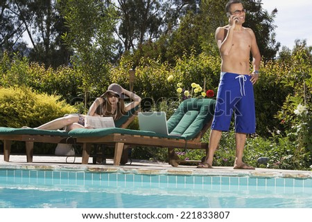 Multi-ethnic couple relaxing next to swimming pool - stock photo