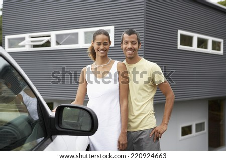 Multi-ethnic couple standing next to car - stock photo
