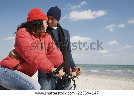 Multi-ethnic couple with bicycle at beach - stock photo