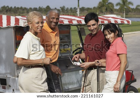 Multi-ethnic couples at food stand on golf course - stock photo