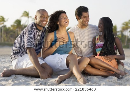 Multi-ethnic couples sitting on beach - stock photo