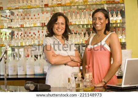Multi-ethnic female sales clerks at perfume store - stock photo