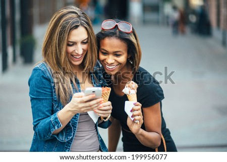 Multi ethnic Friends eating ice cream in city and texting - stock photo