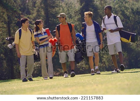 Multi-ethnic friends on golf course - stock photo
