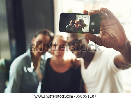 Multi ethnic friends taking a selfie with a phone - stock photo