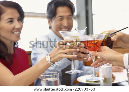 Multi-ethnic friends toasting at restaurant - stock photo