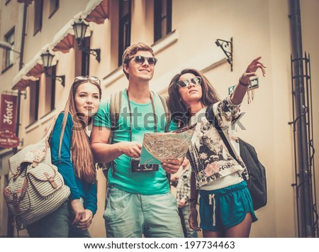 Multi-ethnic friends tourists with map in old city  - stock photo