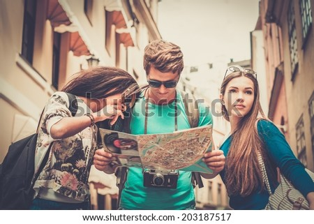 Multi ethnic friends tourists with map in old city  - stock photo