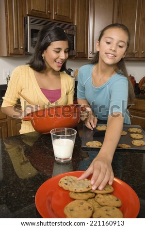 Multi-ethnic girls baking cookies - stock photo